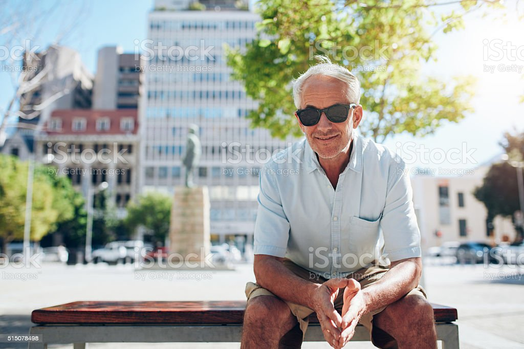 Handsome senior man sitting outdoors in the city stock photo