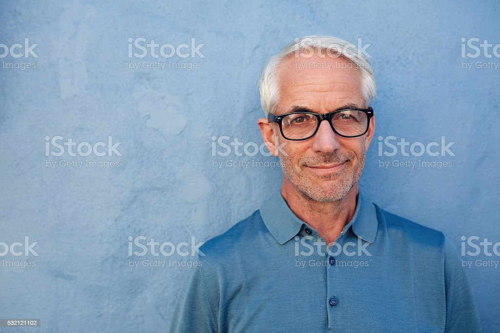 Handsome senior man with glasses looking at camera stock photo