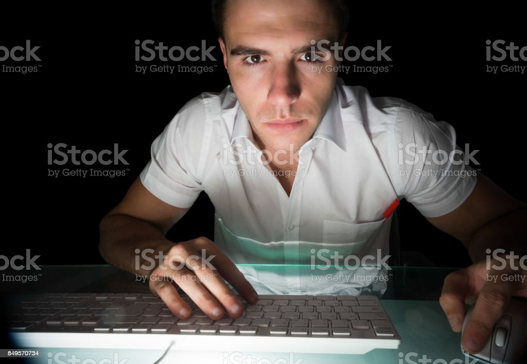 Handsome serious computer engineer working at night at his lit desk