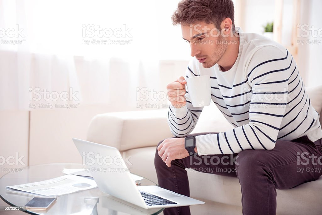 Handsome serious man sitting on the sofa stock photo