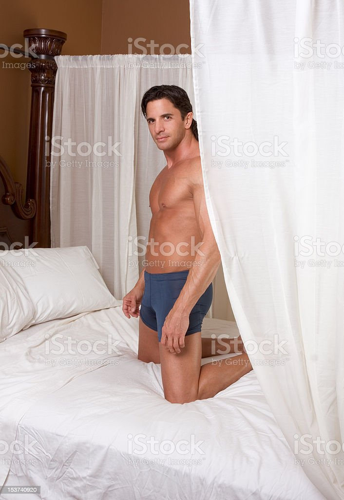 Handsome sexy Caucasian man kneeling on bed. royalty-free stock photo
