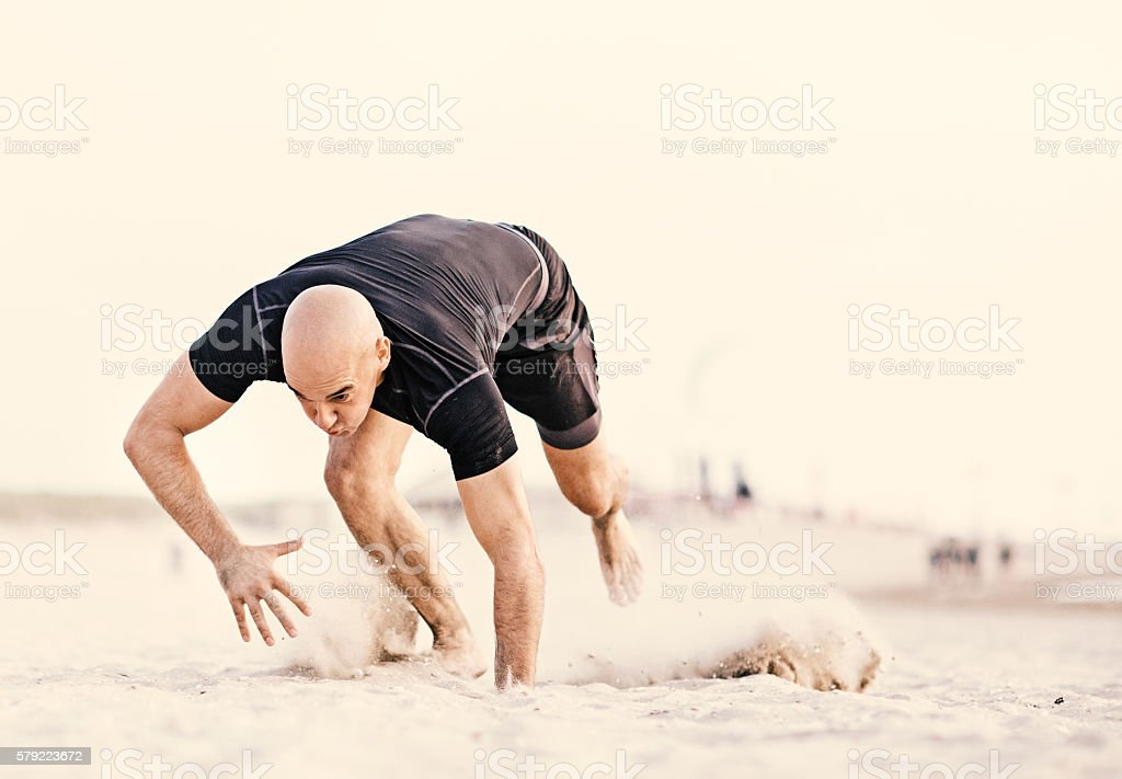 Handsome shaved athletic male working out on sandy beach stock photo