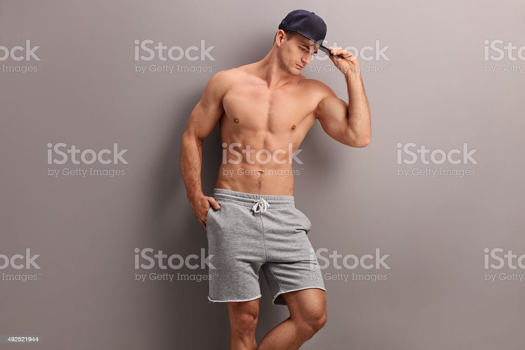 Handsome shirtless man with a blue cap stock photo