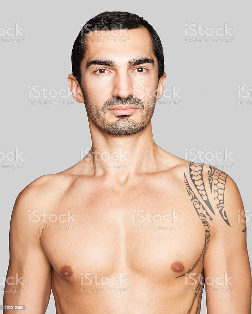 Handsome shirtless man with tattooed shoulder royalty-free stock photo