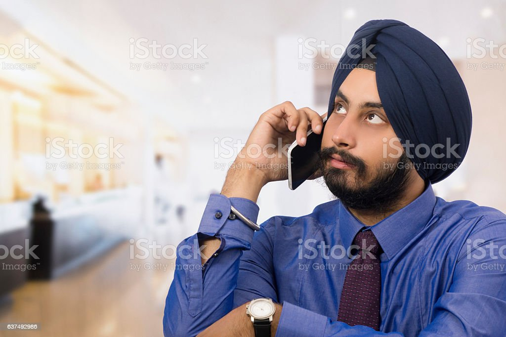Handsome sikh businessman talking on phone stock photo
