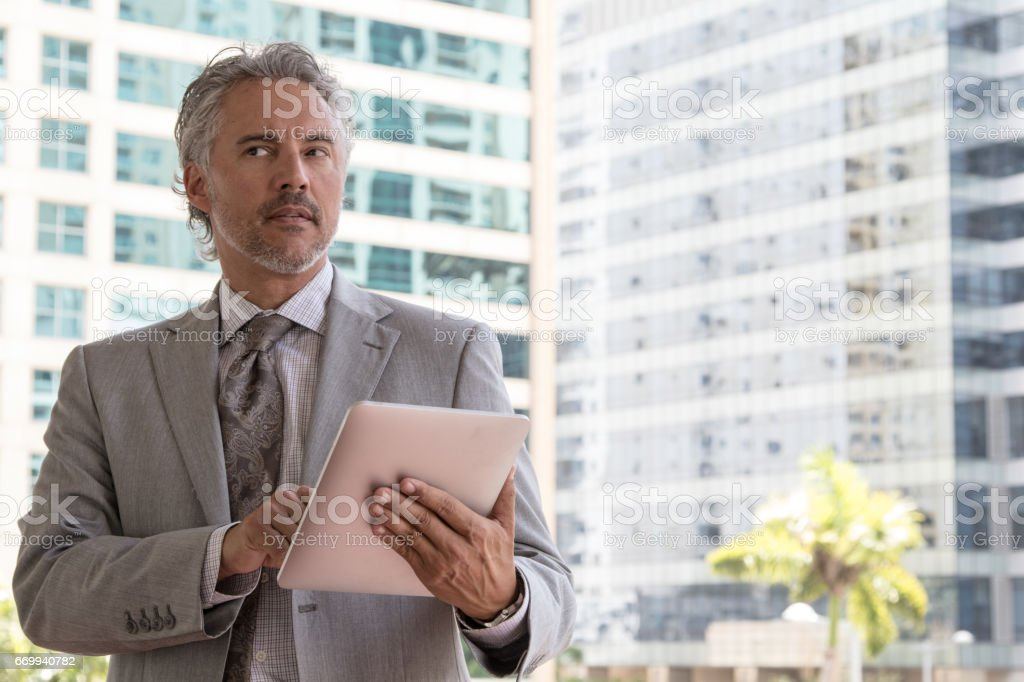 Handsome silver haired businessman downtown stock photo