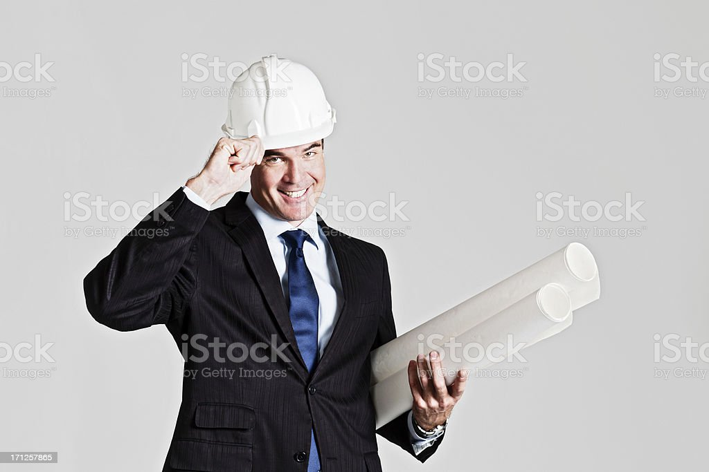 Handsome smiling businessman in hard hat holding rolled-up plans stock photo