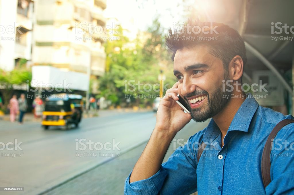 Handsome smiling man talking on mobile phone stock photo