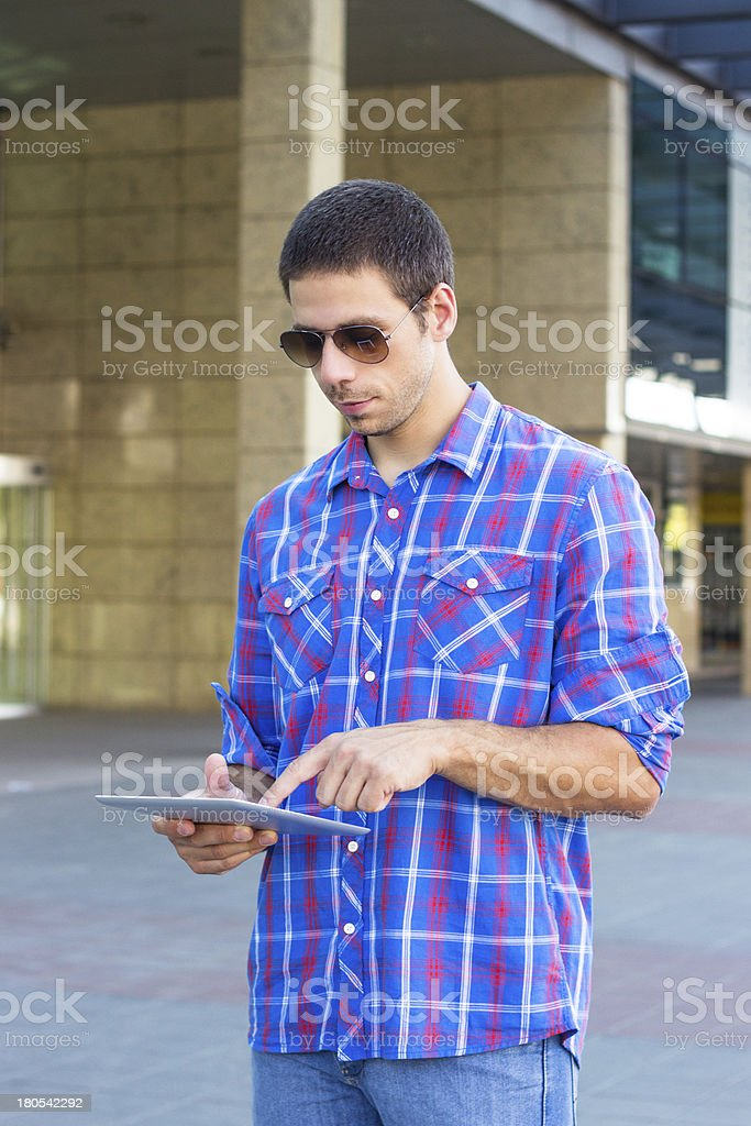 Handsome smiling man using a digital tablet royalty-free stock photo