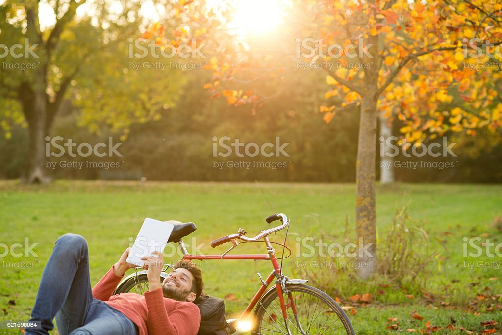 Handsome smiling man using digital tablet at the park stock photo