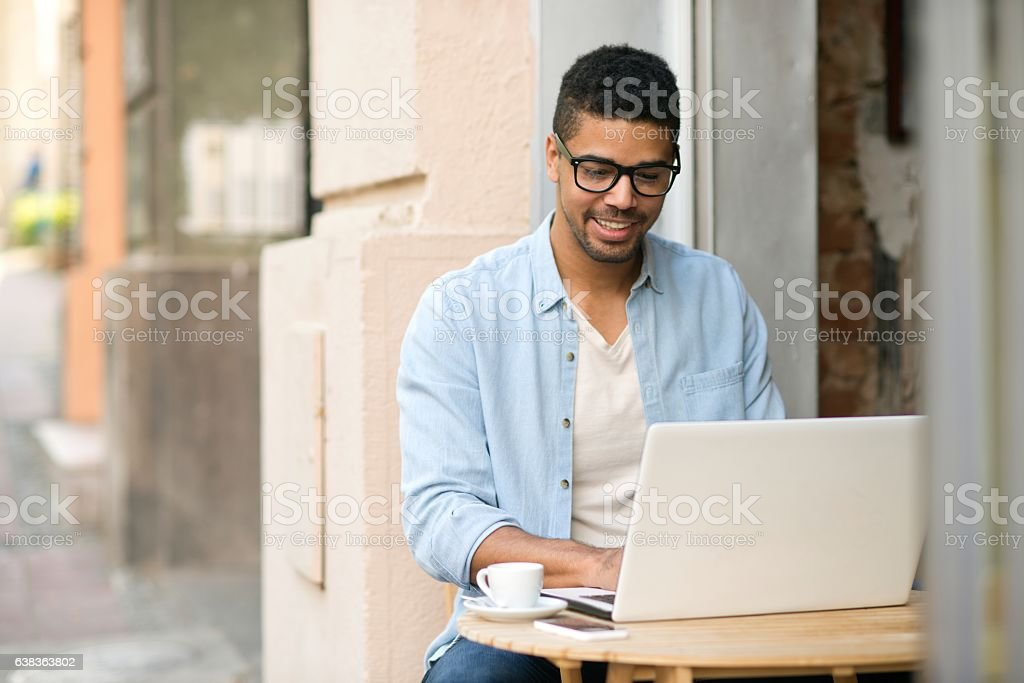 Handsome smiling man using laptop in caffee stock photo