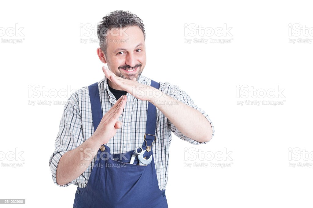 Handsome smiling mechanic making time out gesture stock photo