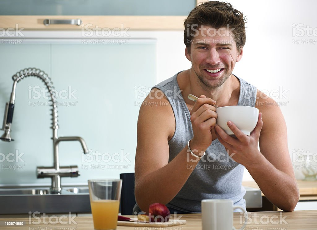 Handsome Smiling Young Man Eating Breakfast royalty-free stock photo