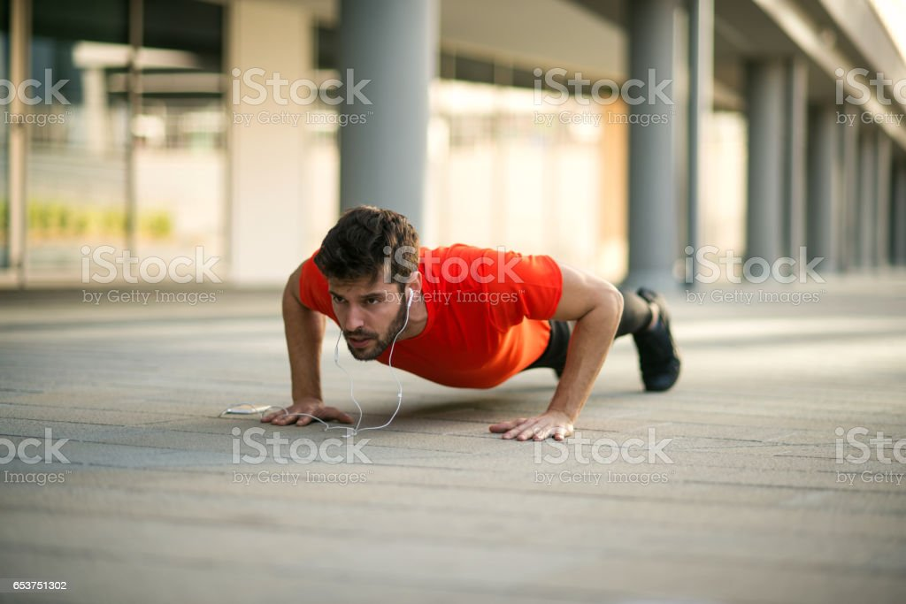 Handsome sportsman doing push ups stock photo
