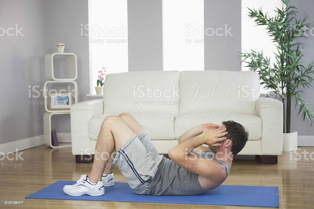 Handsome sporty man doing sit ups stock photo
