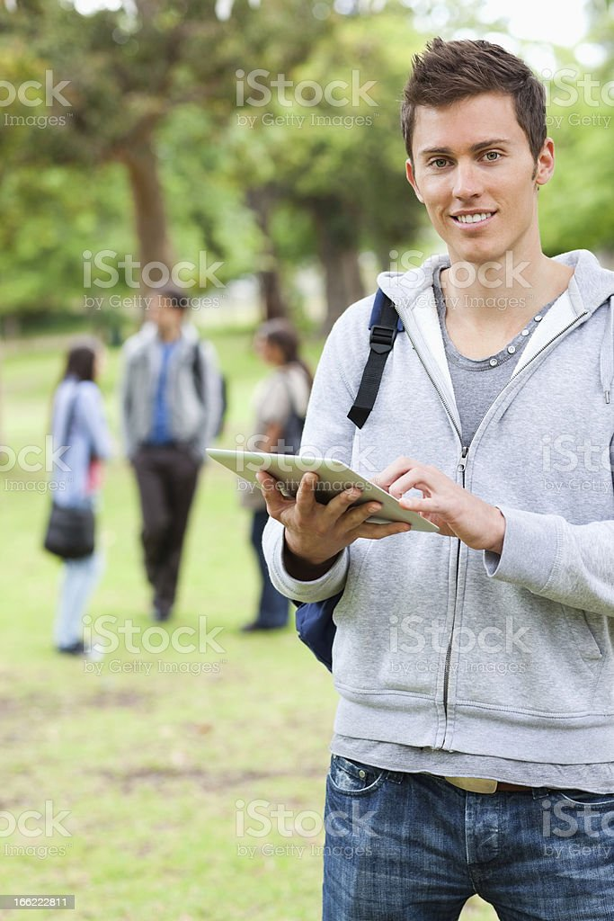 Handsome student using a touch pad royalty-free stock photo