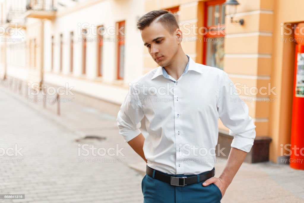 Handsome stylish man in a white elegant shirt and blue pants in the city stock photo