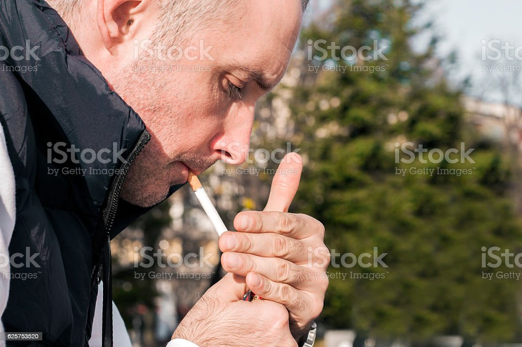 Handsome stylish young man smoking outside in urban setting stock photo