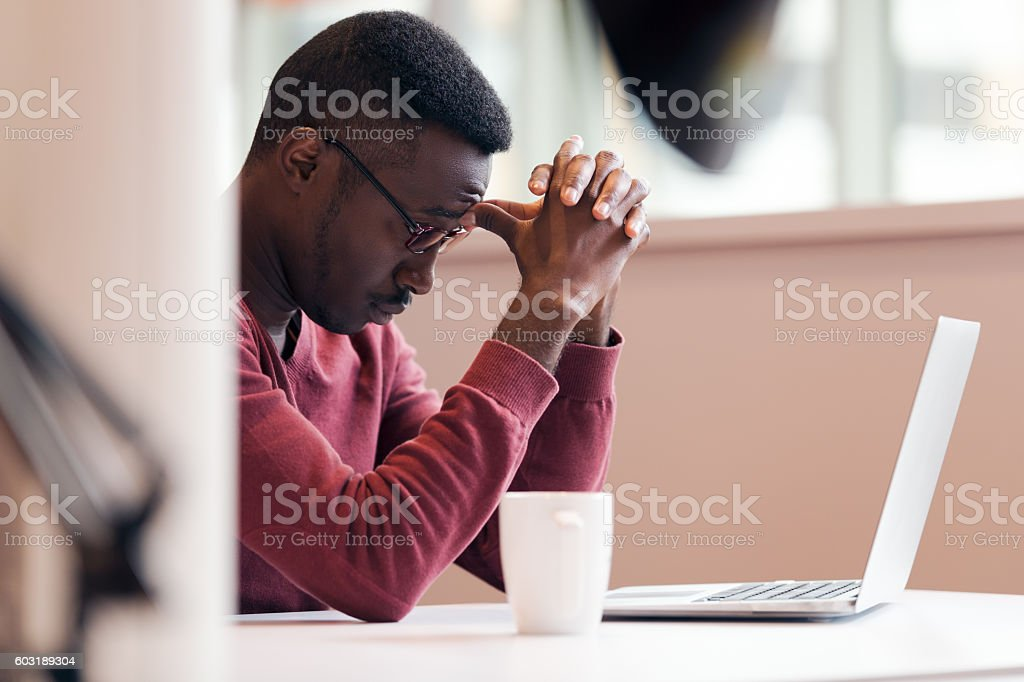 Handsome successful African American looking at the screen stock photo