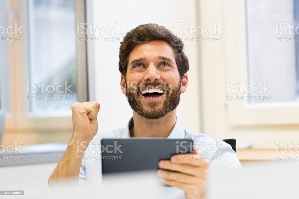 Handsome successful man using digital tablet stock photo