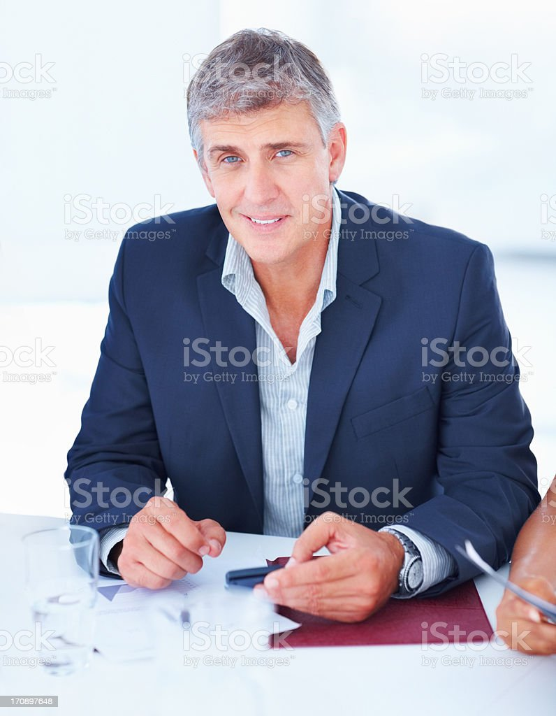 Handsome successful mature business man sitting on a desk royalty-free stock photo