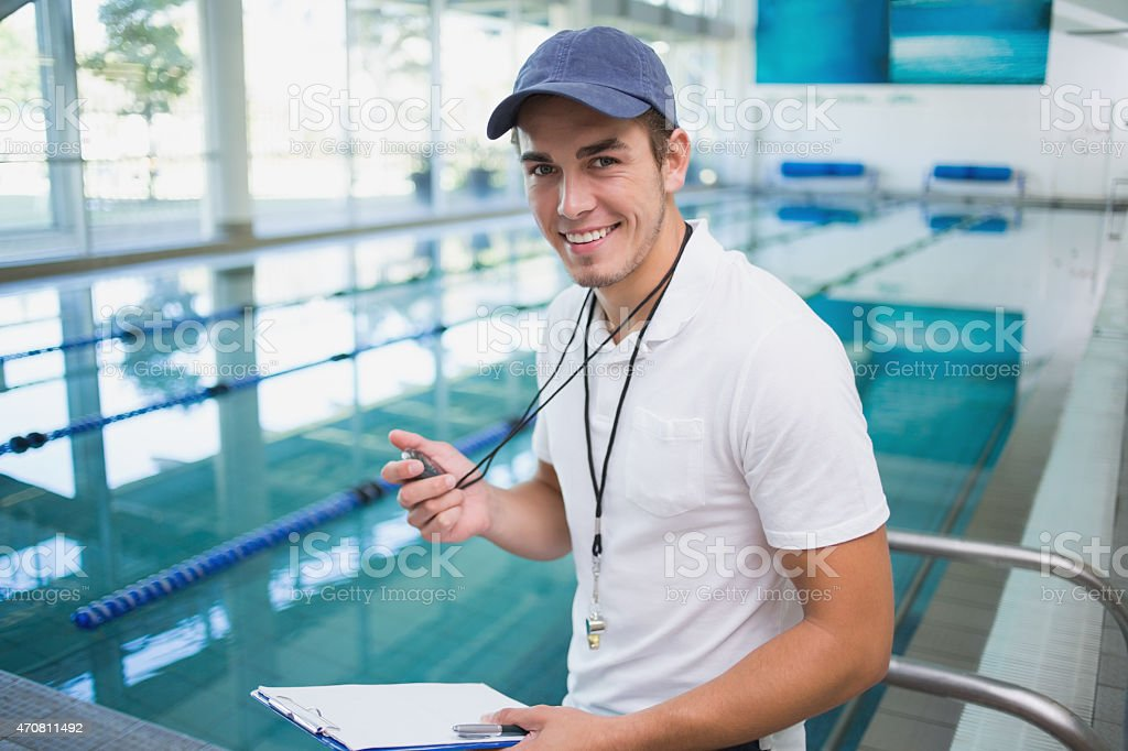 Handsome swimming instructor smiling at camera stock photo