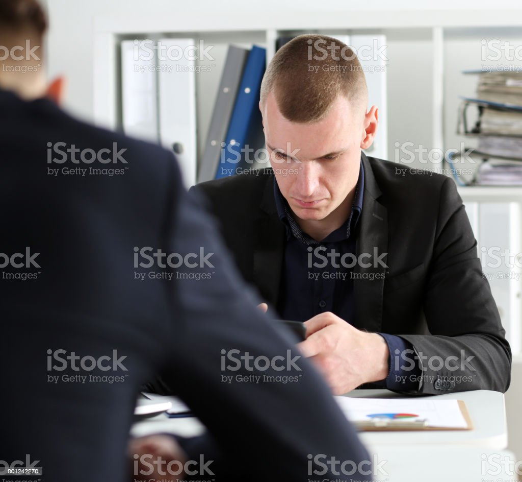 Handsome thoughtful businessman look at cellphone stock photo