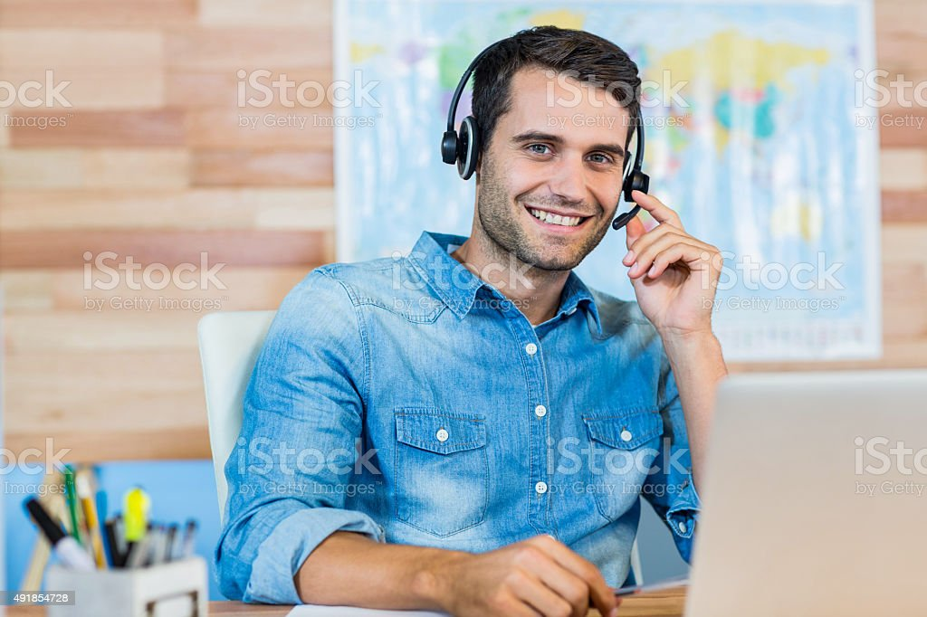 Handsome travel agent smiling at camera stock photo