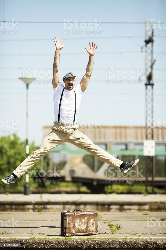 Handsome traveler jumping at the train station royalty-free stock photo