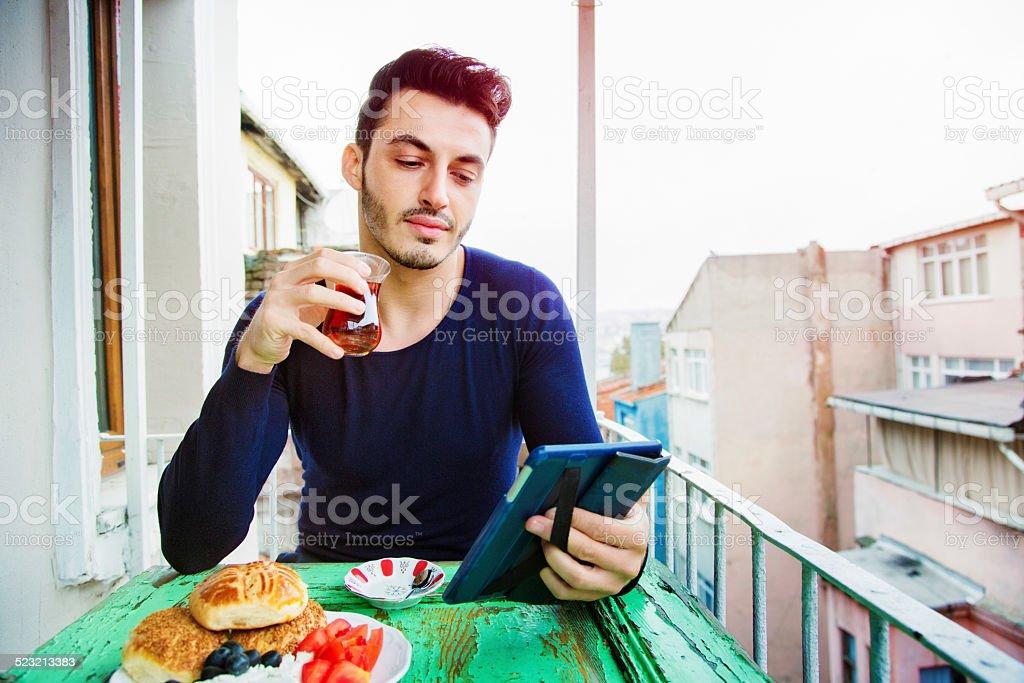 Handsome Turkish man enjoying media on his tablet during breakfast stock photo