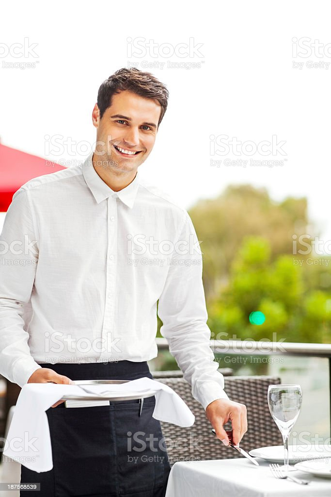 Handsome Waiter Setting Table In Restaurant royalty-free stock photo