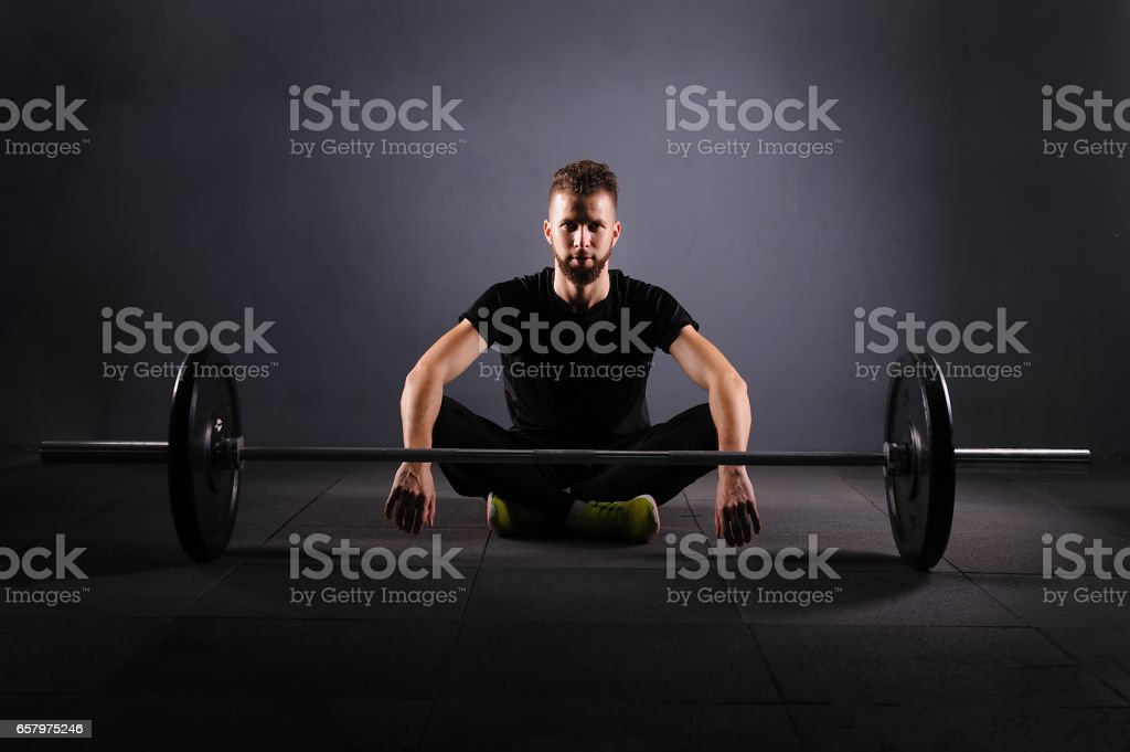 Handsome weightlifter preparing for training. Shallow depth of field, selective focus. Low key stock photo