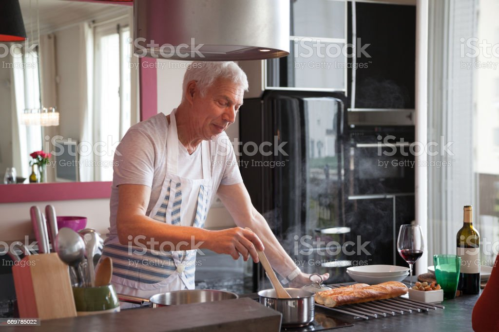 handsome white-haired mature male cooking at home in modern kitchen stock photo