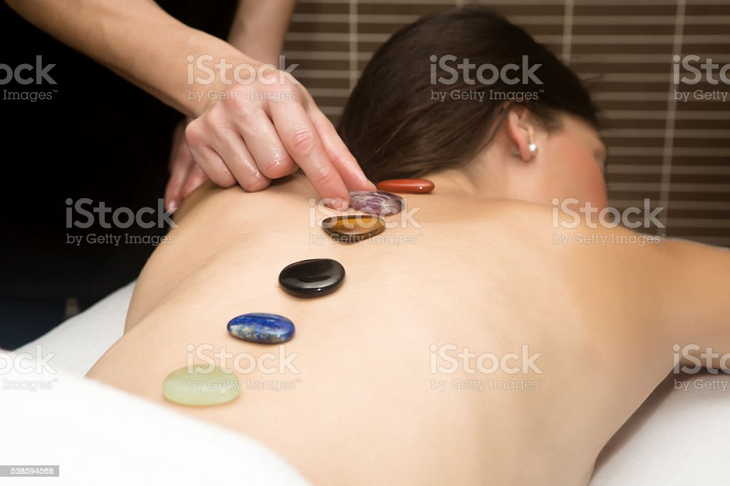 Handsome woman getting massage with hot stones stock photo