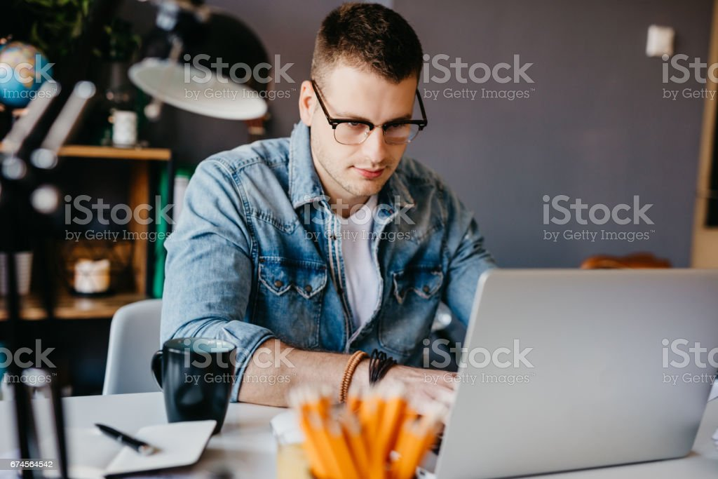 Handsome writer working on the laptop from the home office stock photo