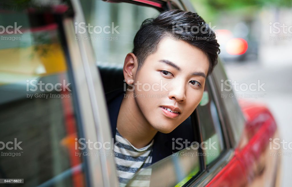 Handsome Young Asian Using Taxi Service in China stock photo