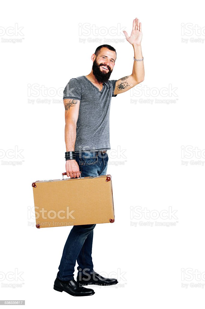 Handsome young bearded man holding a suitcase stock photo