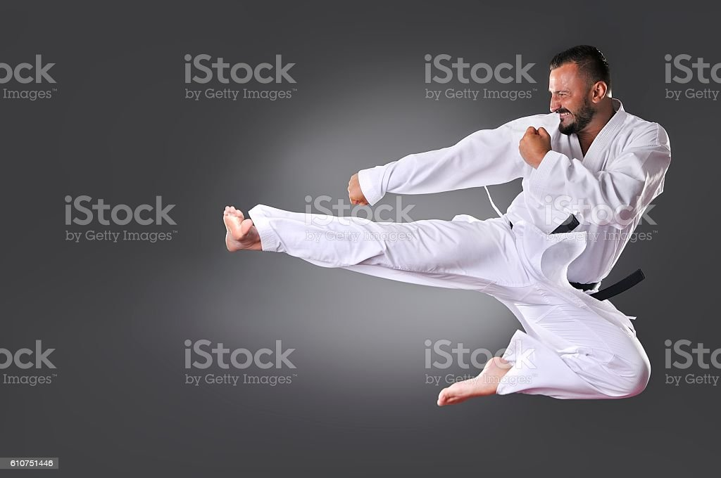 Handsome young black belt male karate doing kick stock photo