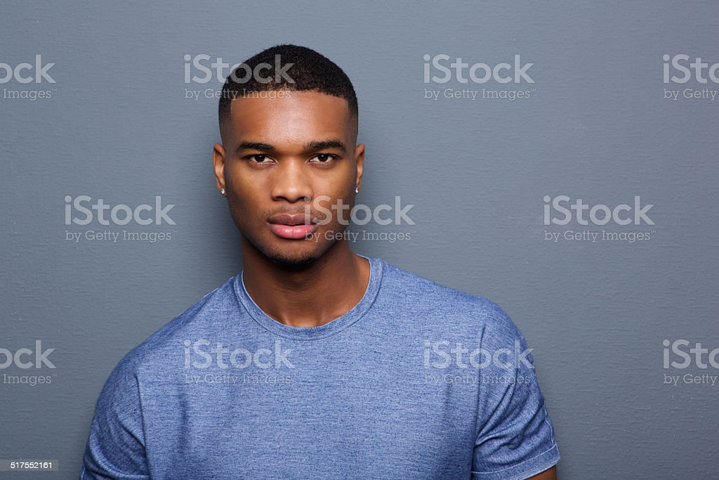 Handsome young black man with serious expression on face stock photo