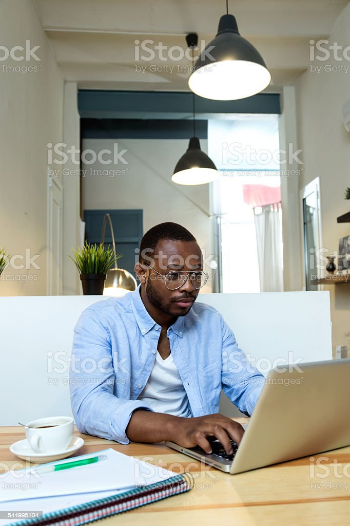 Handsome young black man working with laptop at home. stock photo