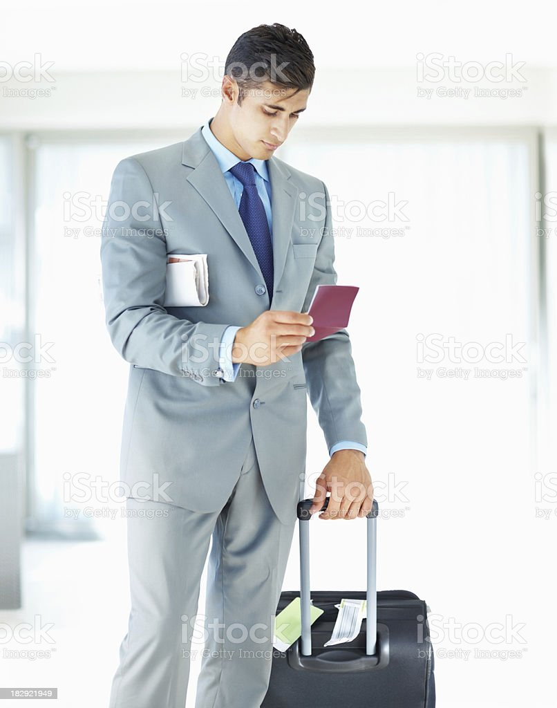 Handsome young business looking at airline ticket royalty-free stock photo