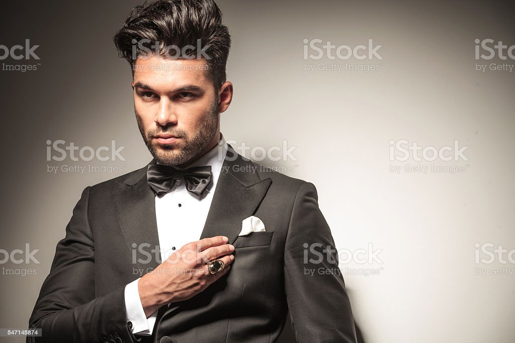 handsome young business man fixing his collar. stock photo