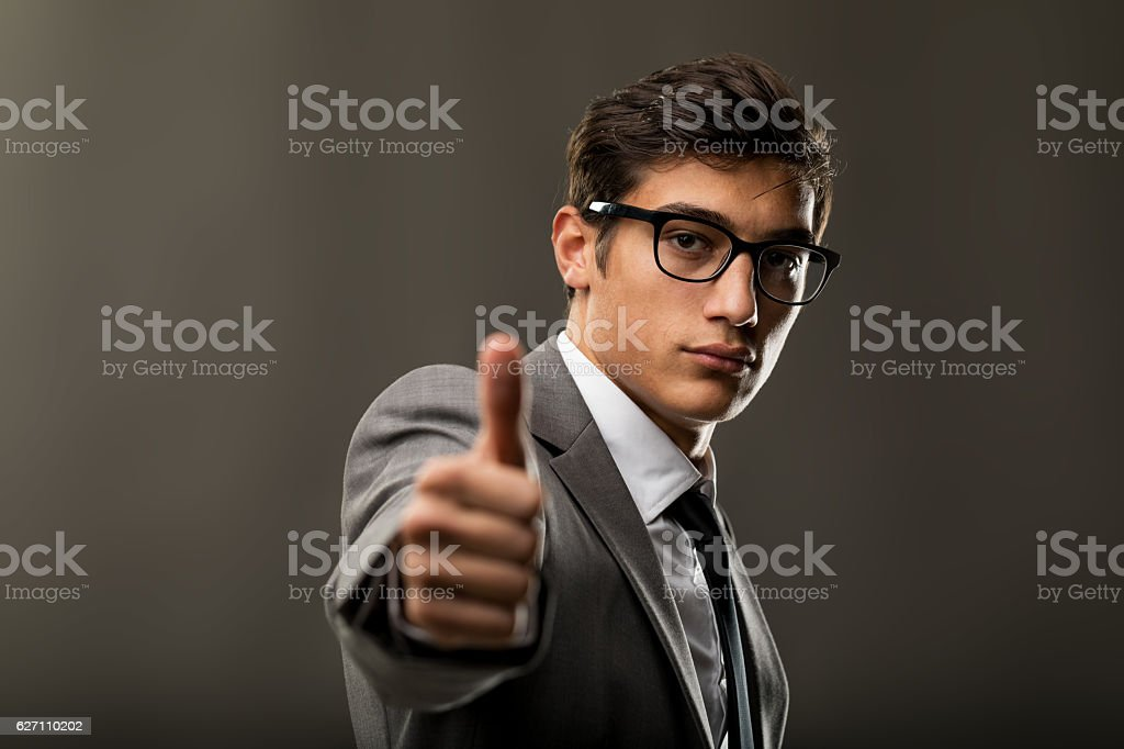 handsome young business man showing thumbs up stock photo