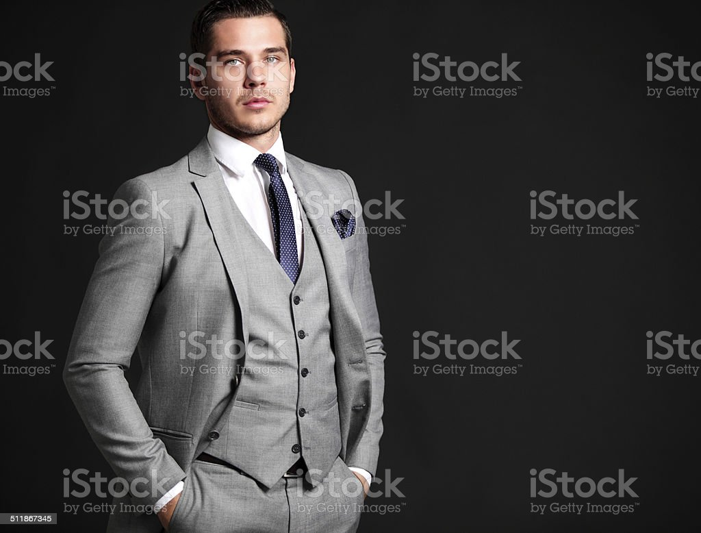 Handsome young business man standing on black background stock photo