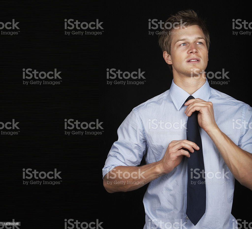 Handsome young businessman adjusting tie royalty-free stock photo