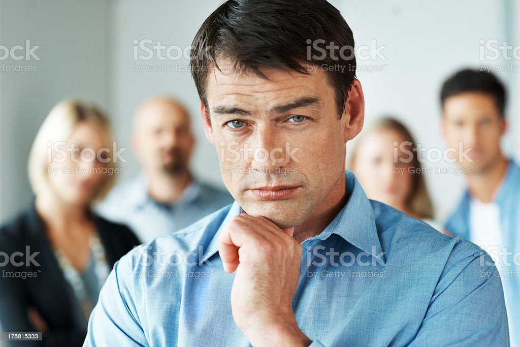 Handsome young businessman standing in office stock photo
