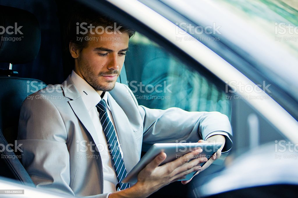 Handsome Young Businessman Using Digital Tablet in Car royalty-free stock photo