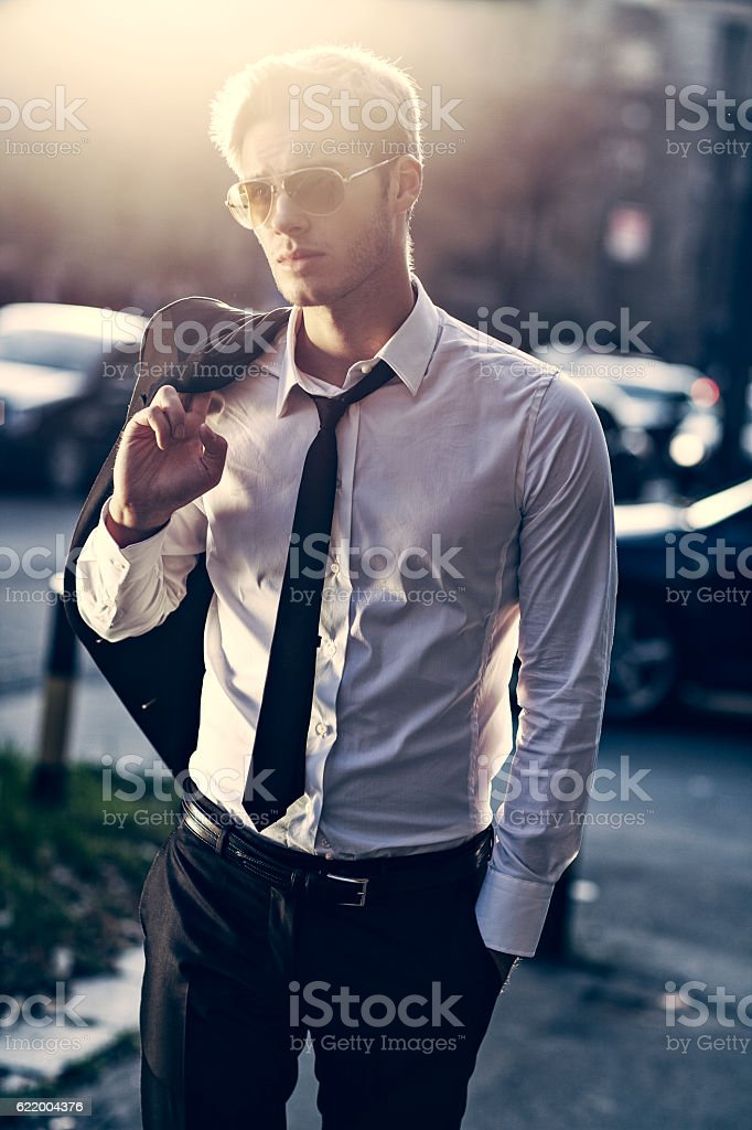 handsome young businessman walking in the street from work stock photo