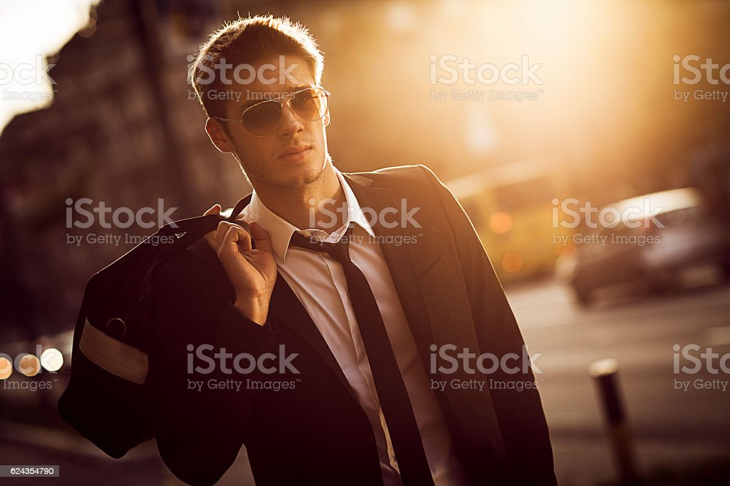 handsome young businessman walking in the street stock photo