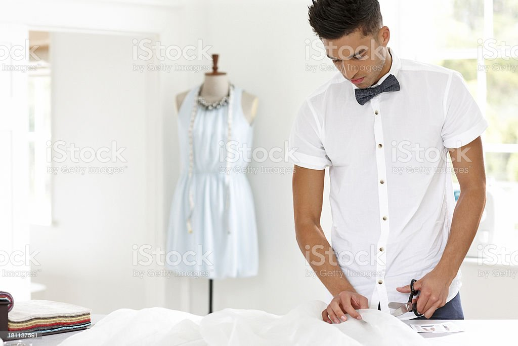 Handsome young fashion designer working in workshop royalty-free stock photo